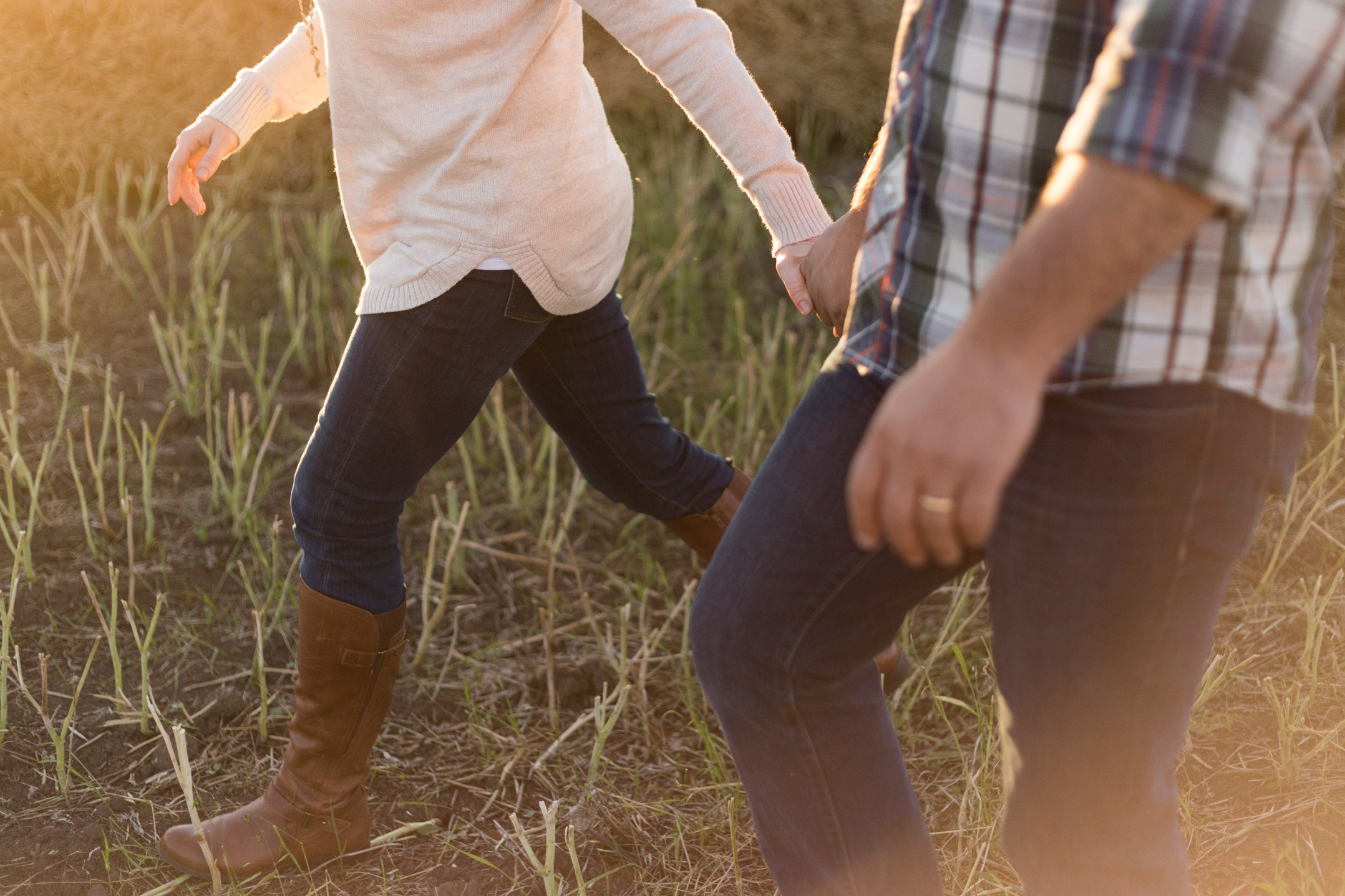 Couple walking through a field. Photo: Prescilla du Preez (Unsplash)