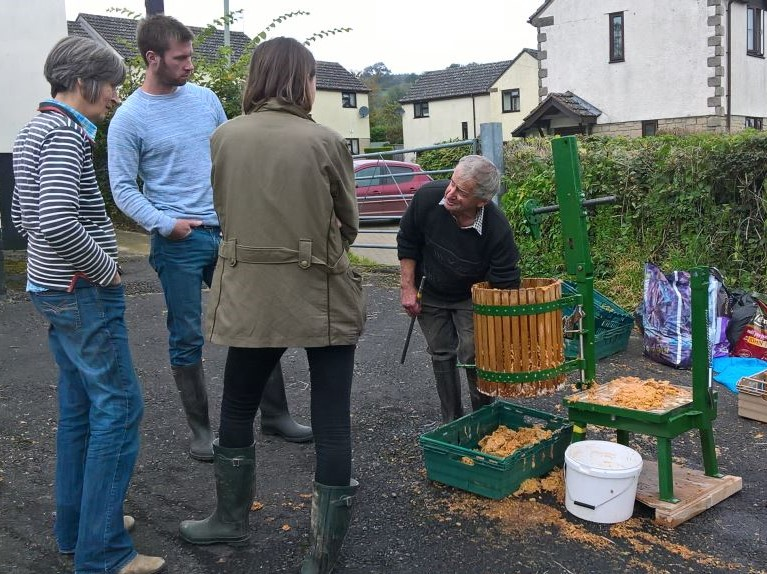 People gathering and pressing apples