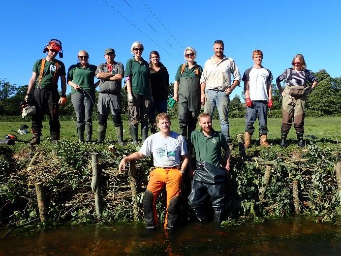 Volunteers standing in front of repaired river bank