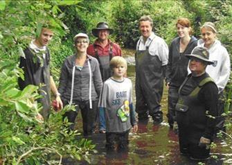 A group of volunteers in waders standing knee deep in river water.