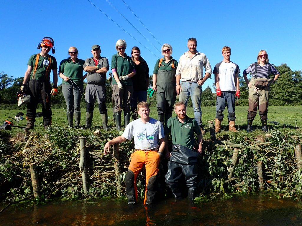 A group of volunteers posing with completed willow structure to repair river bank erosion