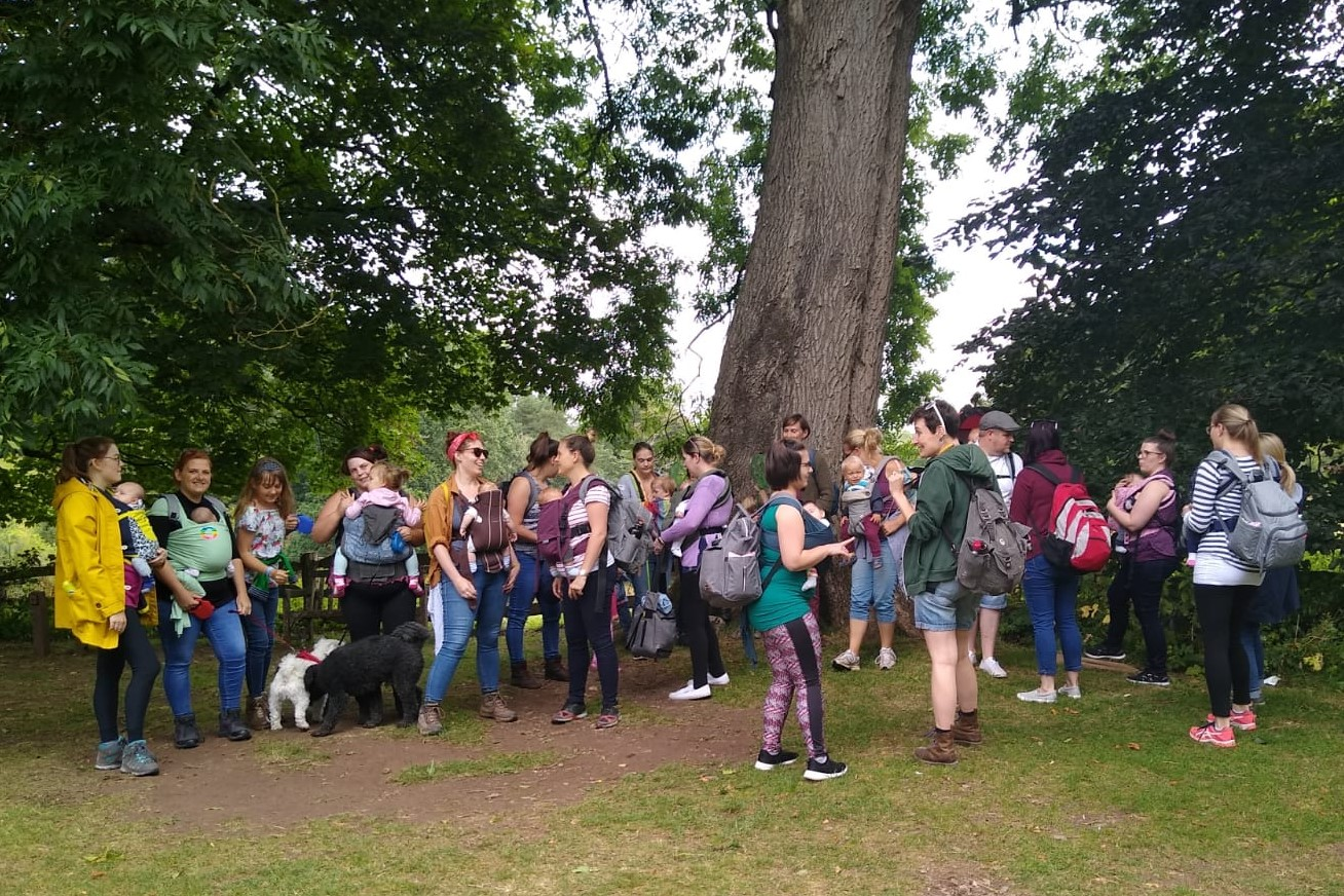 A group of people gathering under a tree with their babies in slings ready for a walk