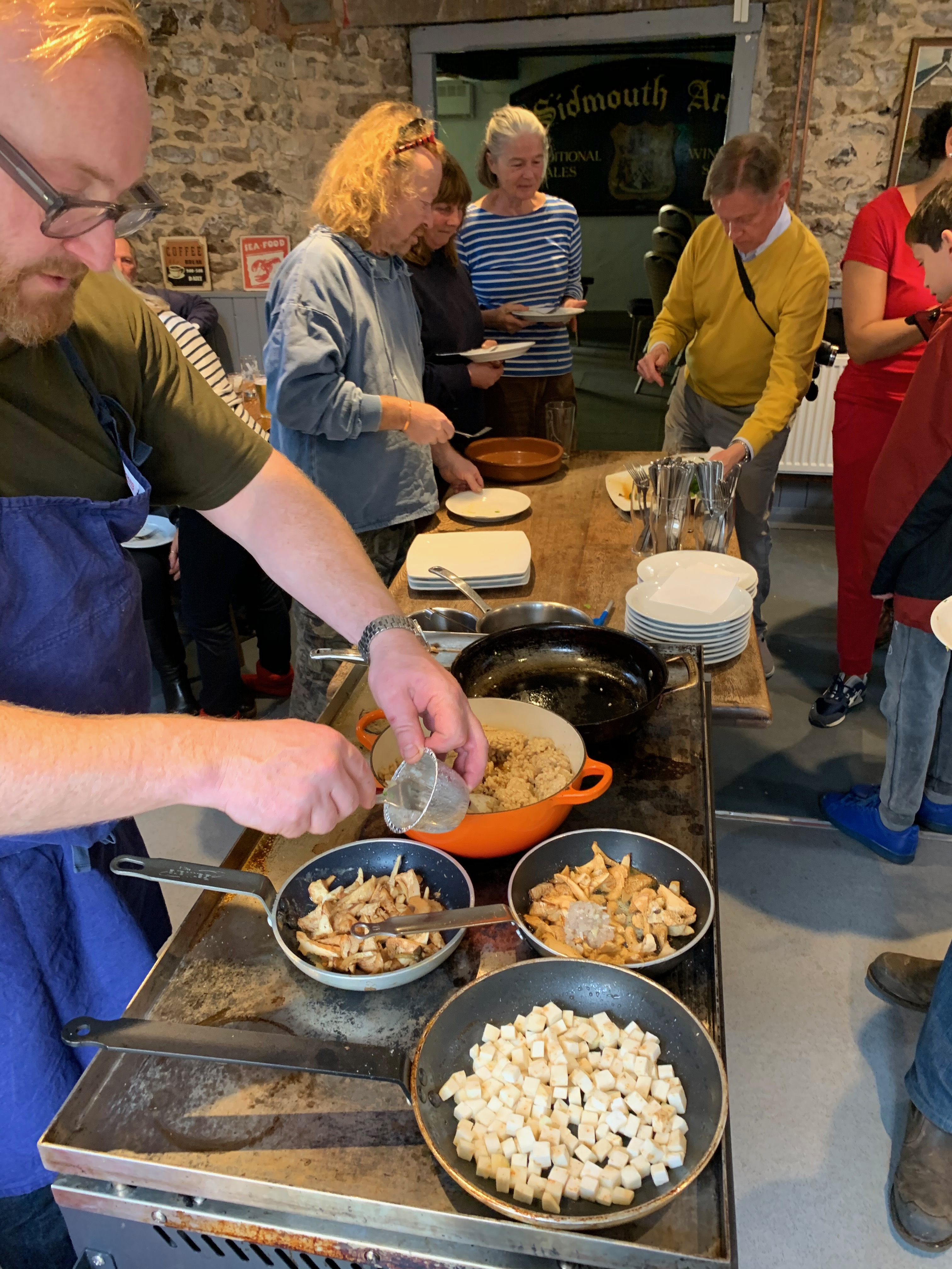 People gather around a table with pots and pans containing a variety of mushroom dishes