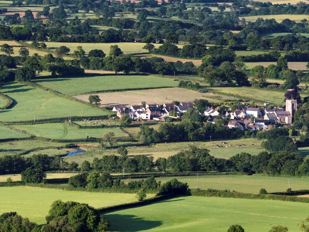 A village set amongst a patchwork of fields and high hedgerows