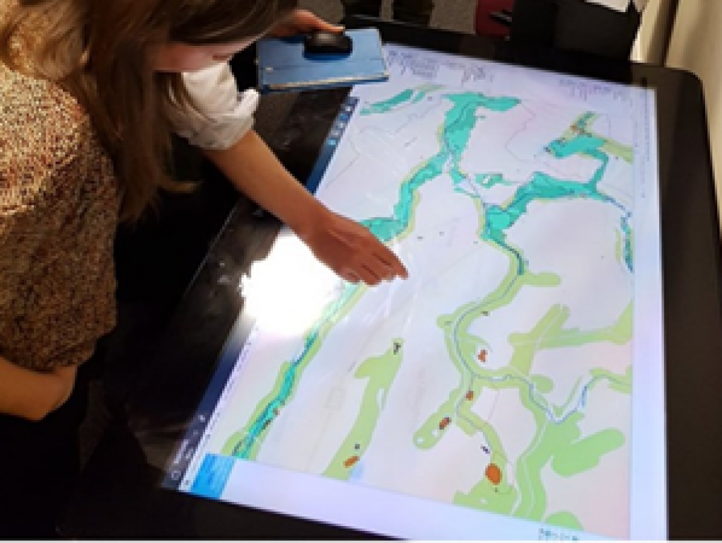 A person using a large interactive map table