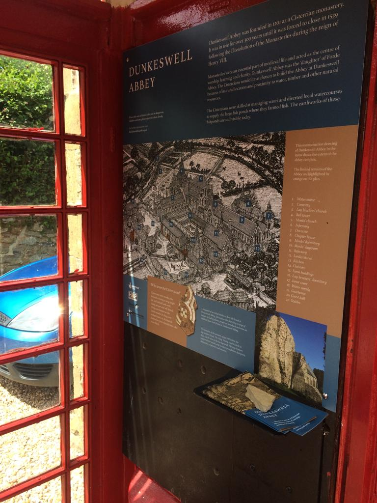 An interpretation board inside a telephone box showing a line drawing of how Dunkeswell Abbey would have looked.