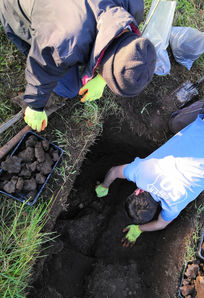 Volunteers look into a deep neatly-cut trench in the ground.