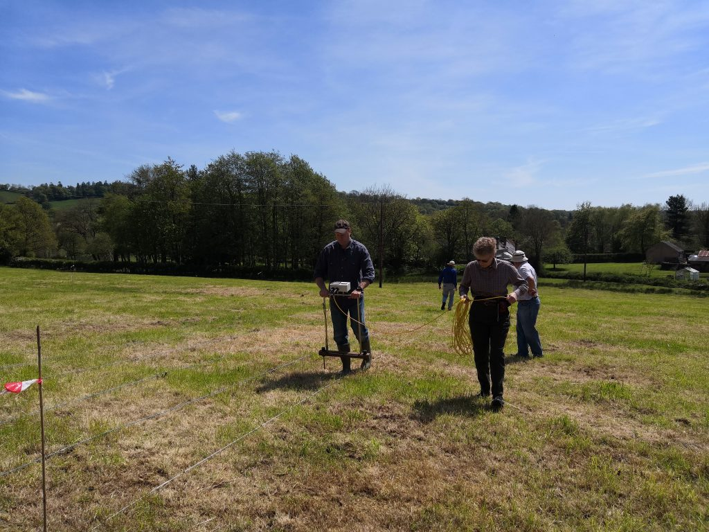 Volunteers using rope and geophysical survey equipment in a field close to Dunkeswell Abbey