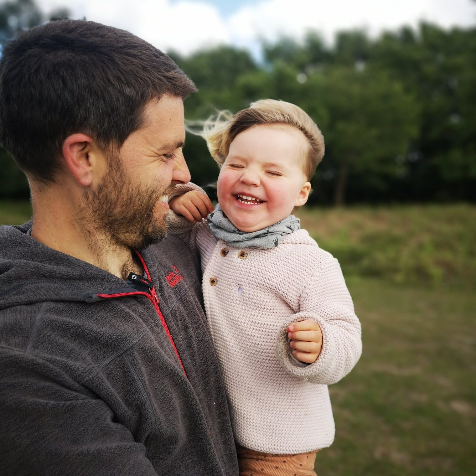 A man holding a small child as they smile and the wind blows through their hair.