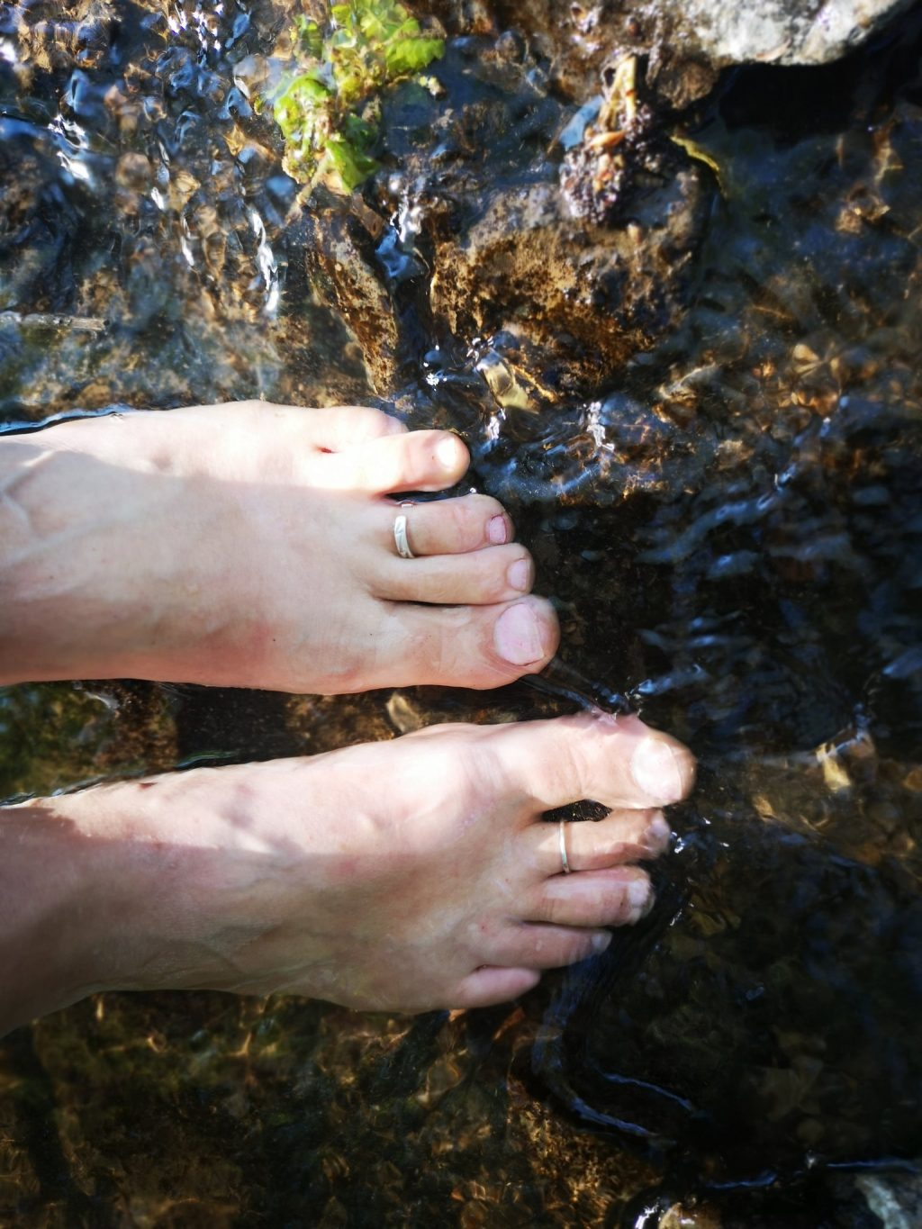 Bare feet paddling in clear shallow water